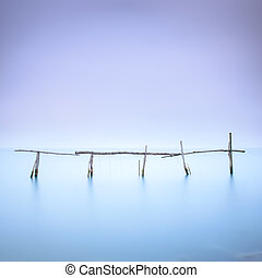 Poles and soft water on water landscape. Long exposure. -...