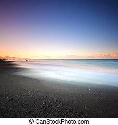 Beach dark sand and sea on morning. Tuscany Italy. Long...