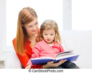 happy mother and daughter with book - family, children,...