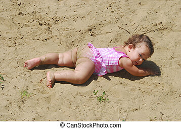 Summer little girl swimsuit sunning at the lake in the sand on the beach