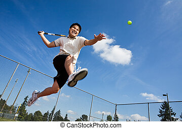 Asian tennis player - An asian tennis player jumping in the...