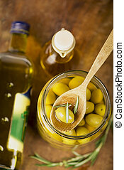 Close up green olives in bank, bottle of olive oil, rosemary...