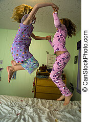 Jumping on a bed - Two girls jumping on a bed in a bedroom...