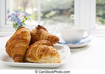 Croissants - Three fresh baked croissants on plate for...