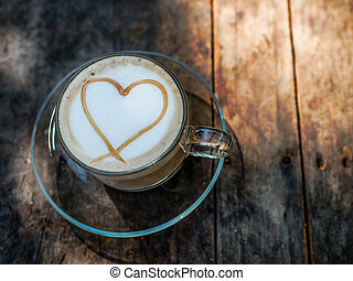 Heart shape on creamy coffee with natural light