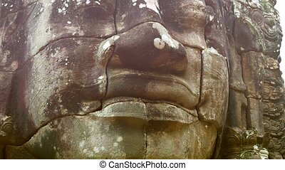 Stone face on the tower of the ancient temple. Bayon....