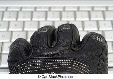 Hacking concept with hand in black leather glove over the...