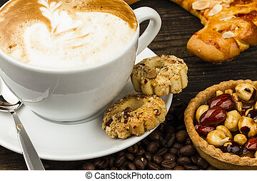 cup of cappucino and cakes on dark background