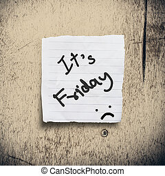 It's Friday on torn paper with wooden background