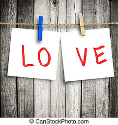 Love on note paper attach to rope with clothes pins on wooden background  with clipping path