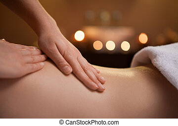 gentle hand massage of girl back. burning candles on...