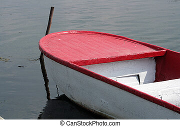 Skiff on a Lake - A small red and white skiff tied to a dock...