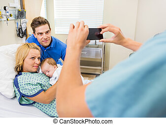 Closeup of female nurse photographing couple with newborn baby through mobilephone in hospital room