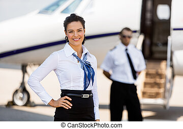 Beautiful Airhostess With Hand On Hip At Airport Terminal -...