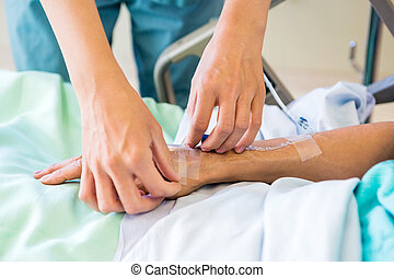 Nurse Starting an IV Line - Cropped image of female nurse...