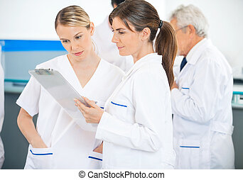 Researchers Discussing Over Clipboard - Female researchers...