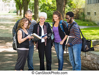 Students Discussing Notes On Campus - Group of multiethnic...