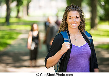Happy Female Student Standing At Campus - Portrait of happy...