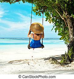 Woman in blue dress swinging at beach - Woman in blue dress...