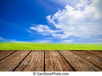 Green field under blue sky. Wood planks floor. Beauty nature...