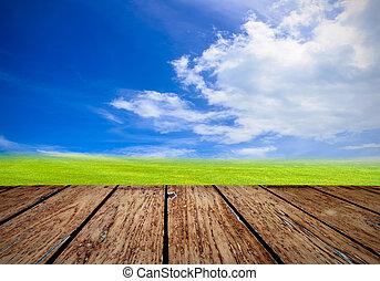 Green field under blue sky. Wood planks floor. Beauty nature...