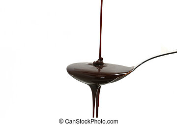 chocolate syrup on spoon - chocolate syrup flowing on a...