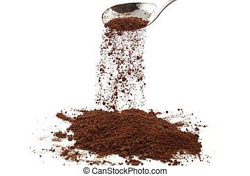 Cocoa powder - cocoa powder trickling of a silver spoon with...