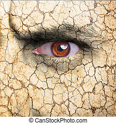 Nature concept - man face covered with cracked earth texture...