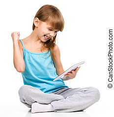 Young girl is playing game using tablet while sitting on...