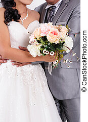 Bride with groom holding wedding bouquet at ceremony