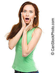 Woman is holding her face in astonishment - Young woman is...
