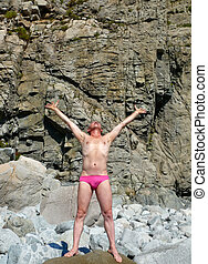 Man on Seacoast 58 - A man sunburns on stone at seacoast. On...