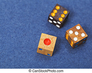 three wooden gambling dices on blue cloth of gaming table