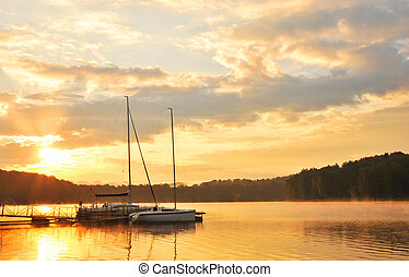 Summer landscape - sunset over lake with boats