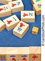 wooden tiles in mahjong game on blue cloth table - wooden...