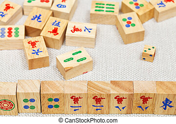wooden tiles in mahjong game on textile table - wooden tiles...