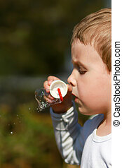 Boy with Bubble Blower - Close-up of young boy blowing...