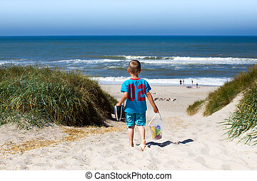 Boy walking towards beach - Young boy overlooking horizon...