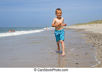 Boy running and smiling at beach - Boy is wearing turquoise...