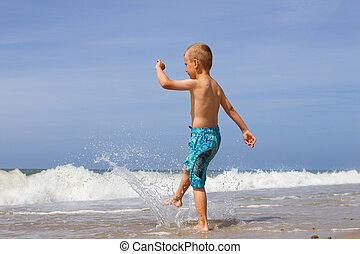Boy splashing water at beach