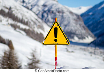 Yellow Danger Sign on Snowy Mountain