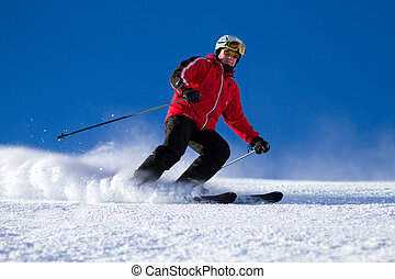 Man skiing on ski slope - Male skier skiing down steep ski...
