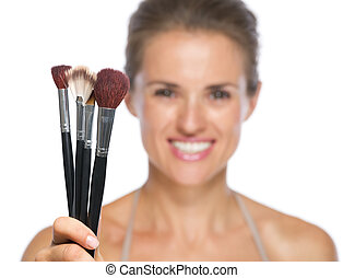 Closeup on young woman showing makeup brushes