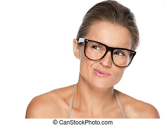 Thoughtful young woman in eyeglasses looking on copy space