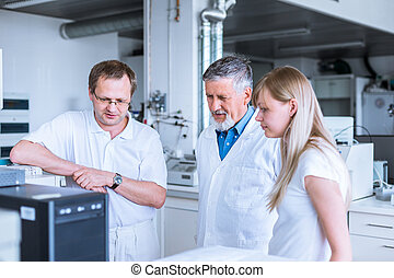 Team of researchers carrying out experiments in a lab