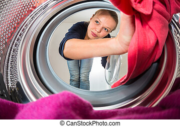 Housework: young woman doing laundry shallow DOF; color...
