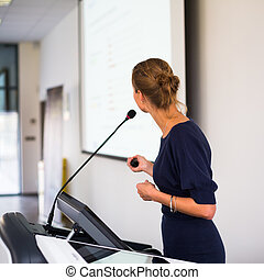 Pretty, young business woman giving a presentation in a...