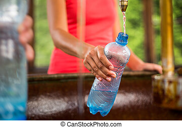 Young woman fillig a plastic bottle with healthy mineral...