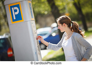 Young woman paying for parking