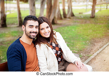 Couple in park - Young romantic couple on a bench in park